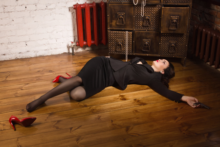 senseless: Detective scene imitation. Woman in a black suit with gun lying on the floor Stock Photo