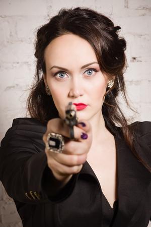 noir: Noir film style woman in a black suit posing with a gun
