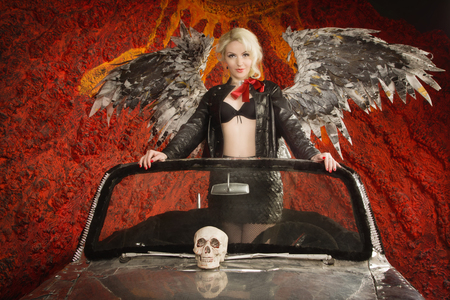 dark angel: Pin Up Girl posing in a Classic Car as dark angel with skull on the road at dusk