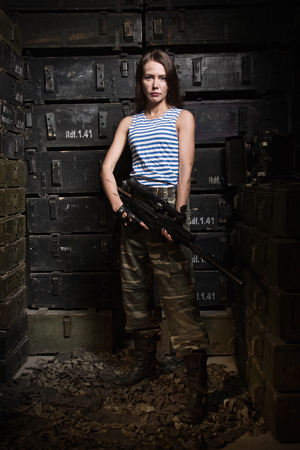russian girl: Russian girl with a gun, posing near the military boxes Stock Photo
