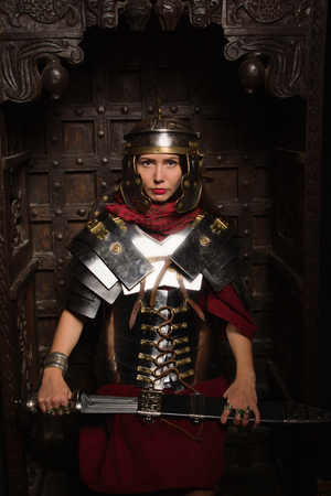 Beautiful woman in roman helmet and armour sitting in a dark interior 写真素材