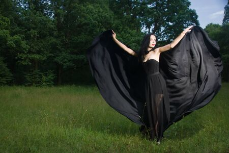 Beautiful brunette woman in black dress and black cloak in the magic forest. Gothic style.