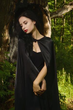 cloak: Beautiful brunette woman in black dress and black cloak in the magic forest. Gothic style.
