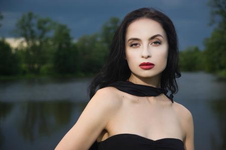 cloak: Beautiful brunette woman in black dress and black cloak. Gothic style.