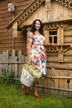 field of daisies: Beautiful adult woman with a bouquet of field daisies. Russian style