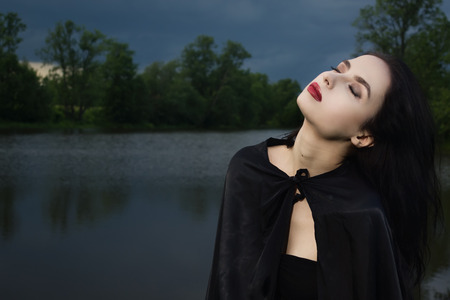 the enchantress: Beautiful brunette woman in black dress and black cloak. Gothic style.