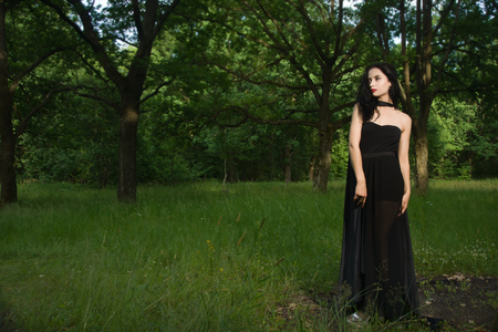 the enchantress: Beautiful brunette woman in black dress and black cloak in the magic forest. Gothic style.