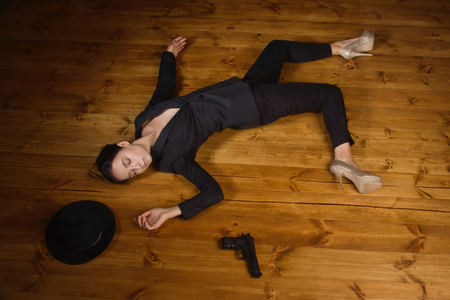 Detective scene imitation. Woman in a black suit with gun lying on the floor Stock Photo