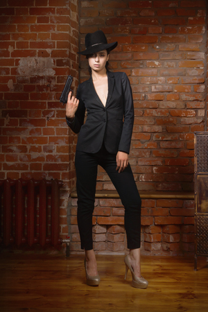 csi: Noir film style woman in a black suit posing with a gun