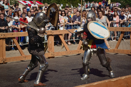 knightly: SAINT-PETERSBURG, RUSSIA - JULY 17, 2016: Battle on a Neva knightly tournament. Armed members in knight armor demonstrating fighting skills on tournament reconstruction.