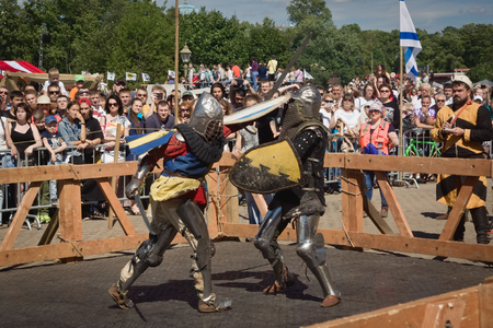 reenacting: SAINT-PETERSBURG, RUSSIA - JULY 17, 2016: Battle on a Neva knightly tournament. Armed members in knight armor demonstrating fighting skills on tournament reconstruction.