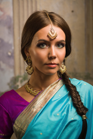 Beautiful young woman in traditional indian clothing with make-up and jewelry. photo