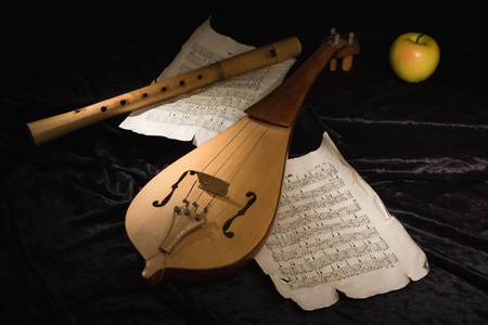 musical score: Renaissance violin (rebec) and alto recorder in a dark room with musical score Stock Photo