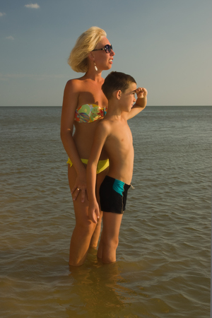 Woman in bikini and young boy kid child relaxing on the beach by the sea Reklamní fotografie