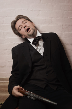 Corpse of killed business man lying on a floor in a bedroom Stock Photo