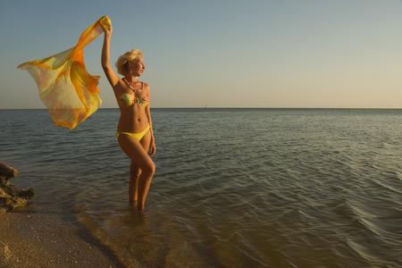 Beautiful woman model in bikini and with pareo at the beach photo