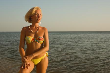 Beautiful woman in bikini relaxing on the beach by the sea photo