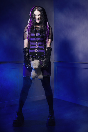cyber girl: Cyber gothic girl with taddy bear in a dark room interior Stock Photo