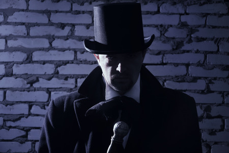 Victorian man in the black coat, top hat and in a tie on a wall background Banco de Imagens