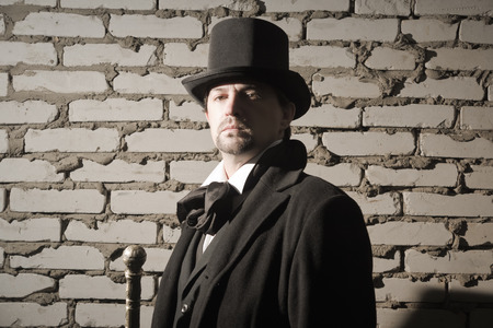 evildoer: Victorian man in the black coat, top hat and in a tie on a wall background Stock Photo