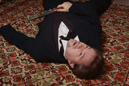 swooned: Corpse of killed business man lying on a floor in a bedroom Stock Photo