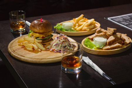 toothpick: Delicious Pub Food. Burgers And Glasses Of Whiskey On Wooden Plates Stock Photo