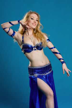 Beautiful belly dancer in a blue suit dance in motion