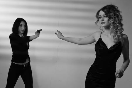 film noir: Film noir. Hitwoman with a gun threatening young beautiful girl