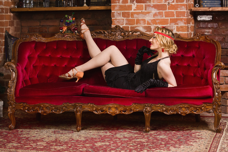old movies: Old movies style: elegant young woman lying on a sofa. Stock Photo