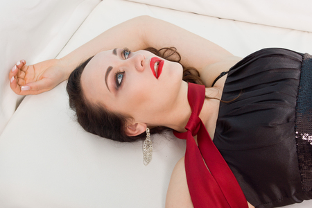 Strangled beautiful woman in black dress lies on the couch. Simulation of the crime scene. Stock Photo