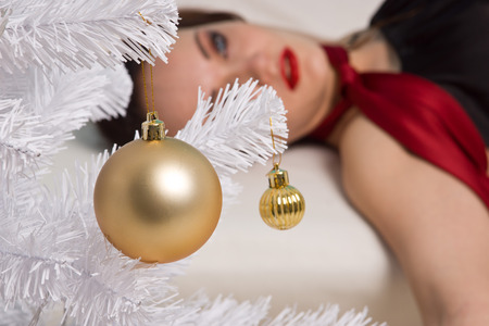Strangled beautiful woman in black dress lies near the Christmas tree on the couch. Simulation of the crime scene. Stock Photo