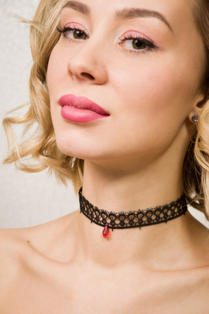 choker: Beautiful woman showing her neck with a choker jewelry on it