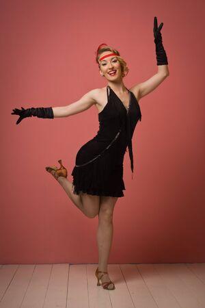 flapper: Precioso años 1920 cosecha dama bailando el charleston en un vestido negro con la venda