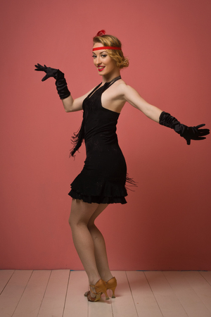 flapper: Gorgeous vintage 1920s lady dancing the charleston in a black dress with headband