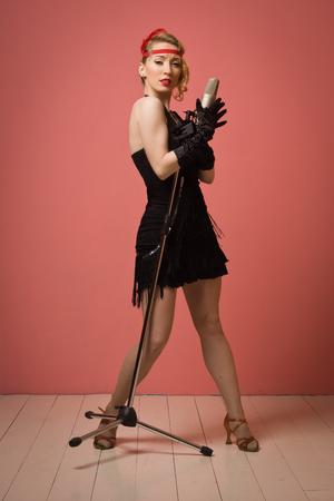 flapper: Señora magnífica 1920 de la vendimia con el micrófono en un vestido negro con la venda Foto de archivo
