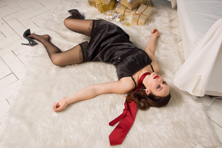 Strangled beautiful woman in black dress lies near the Christmas tree on the floor. Simulation of the crime scene.