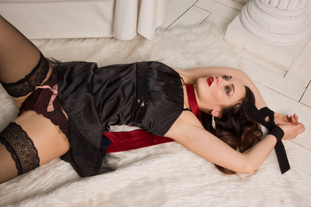 strangled: Strangled beautiful woman in black dress lies on the floor with his hands tied. Simulation of the crime scene.