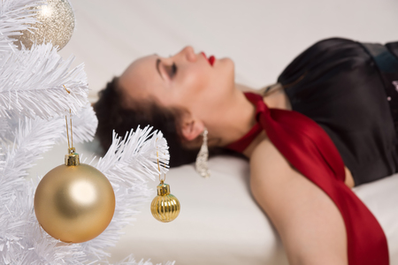 strangled: Strangled beautiful woman in black dress lies near the Christmas tree on the couch. Simulation of the crime scene. Stock Photo