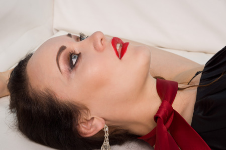 strangled: Strangled beautiful woman in black dress lies on the couch. Simulation of the crime scene. Stock Photo