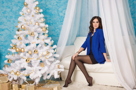 Beautiful Woman sitting on a couch near a Christmas tree Stock Photo