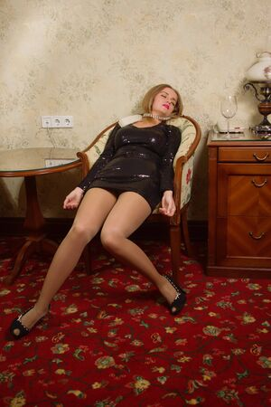 strangled: Strangled beautiful woman in a short black dress in a bedroom. Simulation of the crime scene. Stock Photo