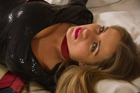 crime: Strangled beautiful woman in a short black dress lies on the bed. Simulation of the crime scene.