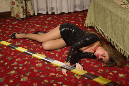Strangled beautiful woman in a short black dress lies on the floor. Simulation of the crime scene. Stock Photo