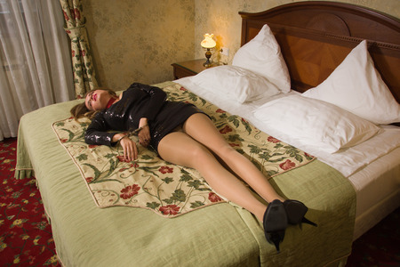 Strangled beautiful woman in a short black dress lies on the bed. Simulation of the crime scene.