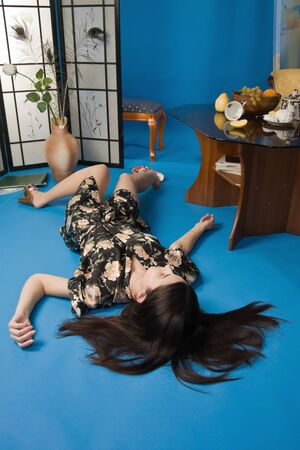 Crime scene simulation: lifeless brunette lying on the floor photo