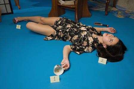 strangled: Crime scene simulation: lifeless brunette lying on the floor