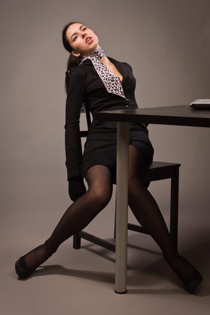 Detective scene imitation. Lifeless woman in a black suit sitting on a office table photo