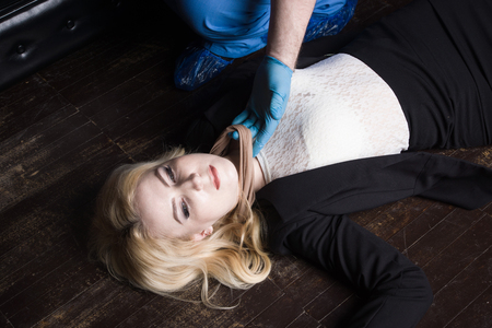 Forensic expert collecting evidence in a crime scene (imitation) Stock Photo