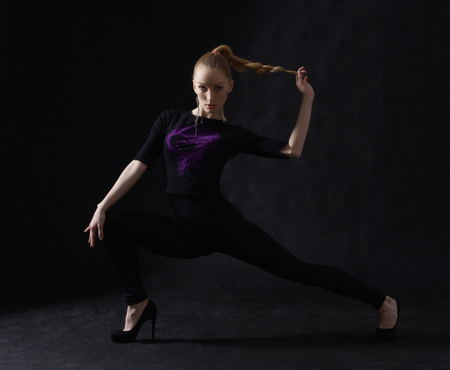 Sexy young vogue dancer posing on dark background
