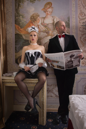 Sexual chambermaid bothers the guest who reads the newspaper.